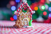 Gingerbread house decorated by sweet candies on a background of bright Christmas tree with garland — Stock Photo
