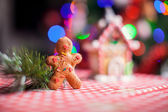 Close-up of gingerbread man background candy ginger house and Christmas tree lights — Stock Photo