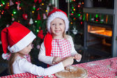 Little girls baking gingerbread cookies in Santa hat — Stock Photo