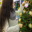 Young woman choosing decorations on the Christmas tree — Stock Photo