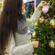 Young woman choosing decorations on the Christmas tree — Stock Photo #37844359