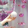 Woman holding white Christmas bauble at store — Stock Photo