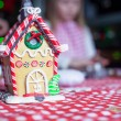 Gingerbread fairy house decorated by colorful candies on a background of little girl — Stock Photo #37844693