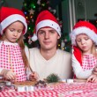 Family baking Christmas gingerbread cookies in the kitchen — Stock Photo #37844699