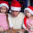 Family baking Christmas gingerbread cookies in the kitchen — Stock Photo #37844711