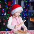 Adorable little girl in Santa hat baking gingerbread Christmas cookies at home — Stock Photo