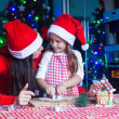 Adorable girl with her mother baking Christmas cookies in the kitchen — Stock Photo #37844887