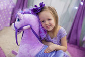 Adorable little girl playing with a toy horse at home — Stock Photo