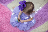 Little adorable girl in a lilac dress among garlands at home — Foto Stock