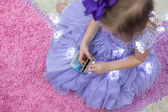 Little adorable girl in beautiful dress among garlands at home — Foto de Stock
