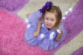 Little adorable girl in a lilac dress among garlands at home — Foto de Stock