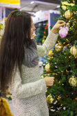 Young woman choosing decorations on the Christmas tree — Foto de Stock