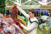 Young man choosing decorations on the Christmas tree — Foto Stock