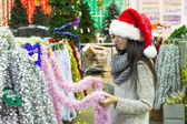 Young woman in santa hat choosing decorations on the Christmas tree — Stok fotoğraf