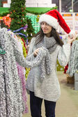 Young woman in santa hat choosing decorations on the Christmas tree — Foto de Stock