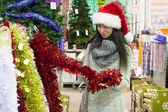 Young woman in santa hat choosing decorations on the Christmas tree — Foto Stock
