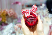 Beautiful red ball in hands of a young woman for Christmas — Foto Stock