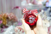 Beautiful red ball in hands of young woman for Christmas — Stock fotografie