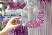 Woman holding Christmas glass bowl with small pink balls at store — Stock fotografie