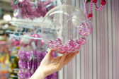 Woman holding Christmas glass bowl with small pink balls at store — Foto de Stock