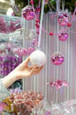Woman holding white Christmas bauble at store — Foto de Stock