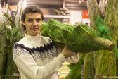 Young man in Santa hat choose christmas tree — Stock Photo