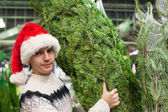 Young man buying a Christmas tree in the store — Foto Stock