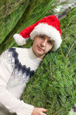Young man choose a Christmas tree in the store — Foto Stock
