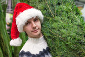 Close-up Young man buying a Christmas tree in the store — Foto de Stock