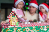 Gingerbread fairy house decorated by colorful candies on a background of happy family — Stock Photo