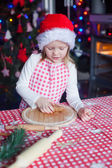 Adorable little girl with rolling pin baking gingerbread cookies for Christmas — Stock Photo