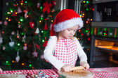 Little girl with rolling pin baking Christmas gingerbread cookies — Stock Photo