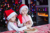 Cute little girls preparing gingerbread Christmas cookies in the kitchen — Stock Photo