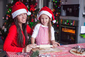 Little adorable girl and young mother baking Christmas gingerbread cookies at home — Stock Photo