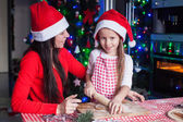 Young mother and little daughter in kitchen making Christmas cookies. — Stock Photo