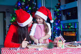 Adorable girl with her mother baking Christmas cookies in the kitchen — Stock Photo
