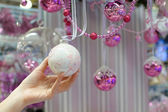 Woman holding white Christmas bauble at store — Foto Stock