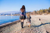 Little girl and her mother walking on the beach in winter sunny day — Stock Photo