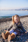 Adorable little girl on the beach having fun at warm winter day — Stock Photo