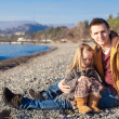 Stock Photo: Young father and little girl at beach on sunny winter day