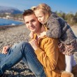 Portrait of a adorable girl hugging his young father at the beach — Stock Photo #39052343