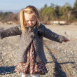Stock Photo: Adorable little girl spread her arms on beach in winter sunny day
