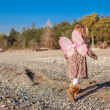 Adorable little girl with butterfly wings running along the beach in a winter sunny day — Stock Photo #39052707
