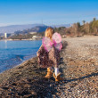Little girl with butterfly wings running along the beach in a winter sunny day — Stock Photo #39052763