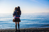 Mother and little girl at beach in sunny winter day — Stock Photo