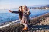 Bambina con mamma divertirsi sulla spiaggia in una giornata invernale — Foto Stock