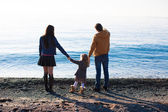 Young parents with their little daughter at beach in the cold period — Stock Photo