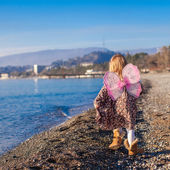 Adorable little girl with butterfly wings running along the beach in a winter sunny day — Stock Photo