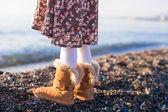 Closeup de pernas menina em fundo de botas de pêlo acolhedor do mar — Fotografia Stock