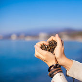 Woman hands holding small stones form heart shape background the sea — Foto de Stock